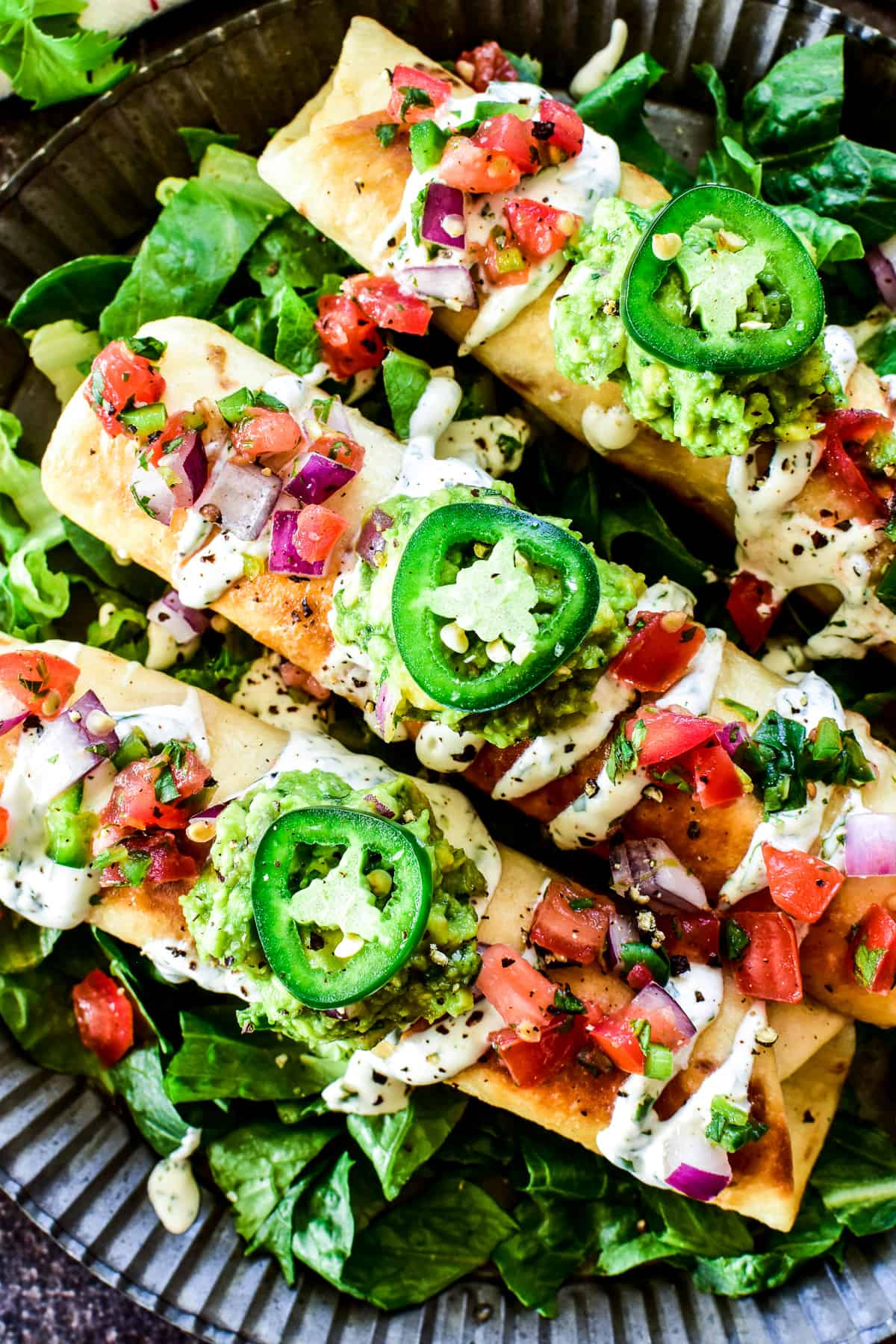 Overhead close up of Creamy Chicken Flautas loaded with toppings