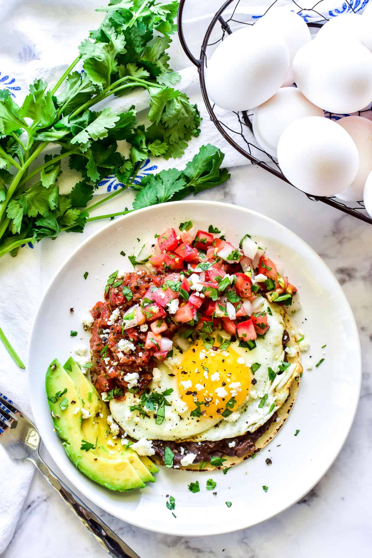 Overhead shot of Huevos Rancheros with a basket of eggs and fresh cilantro
