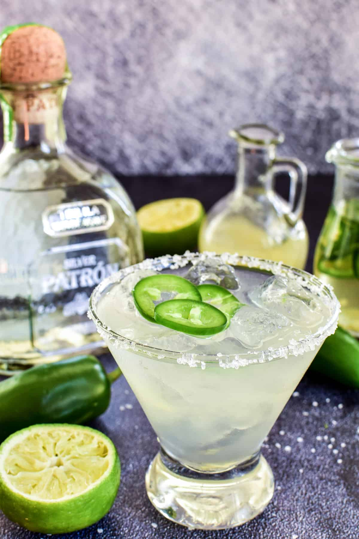 Jalapeño Margarita with limes, jalapeños, and a bottle of Patron