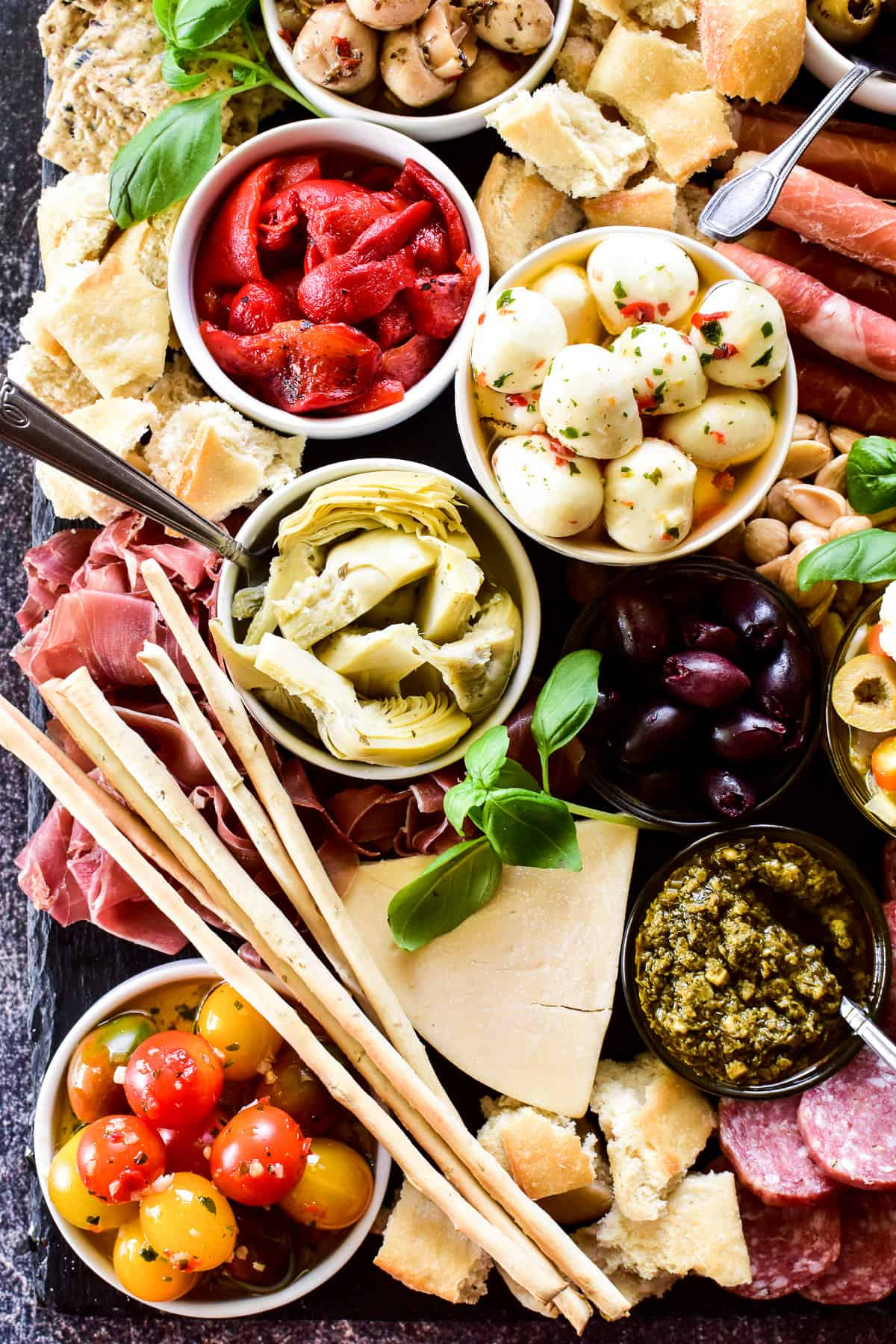 Overhead shot of veggies, meats and cheeses on antipasto platter