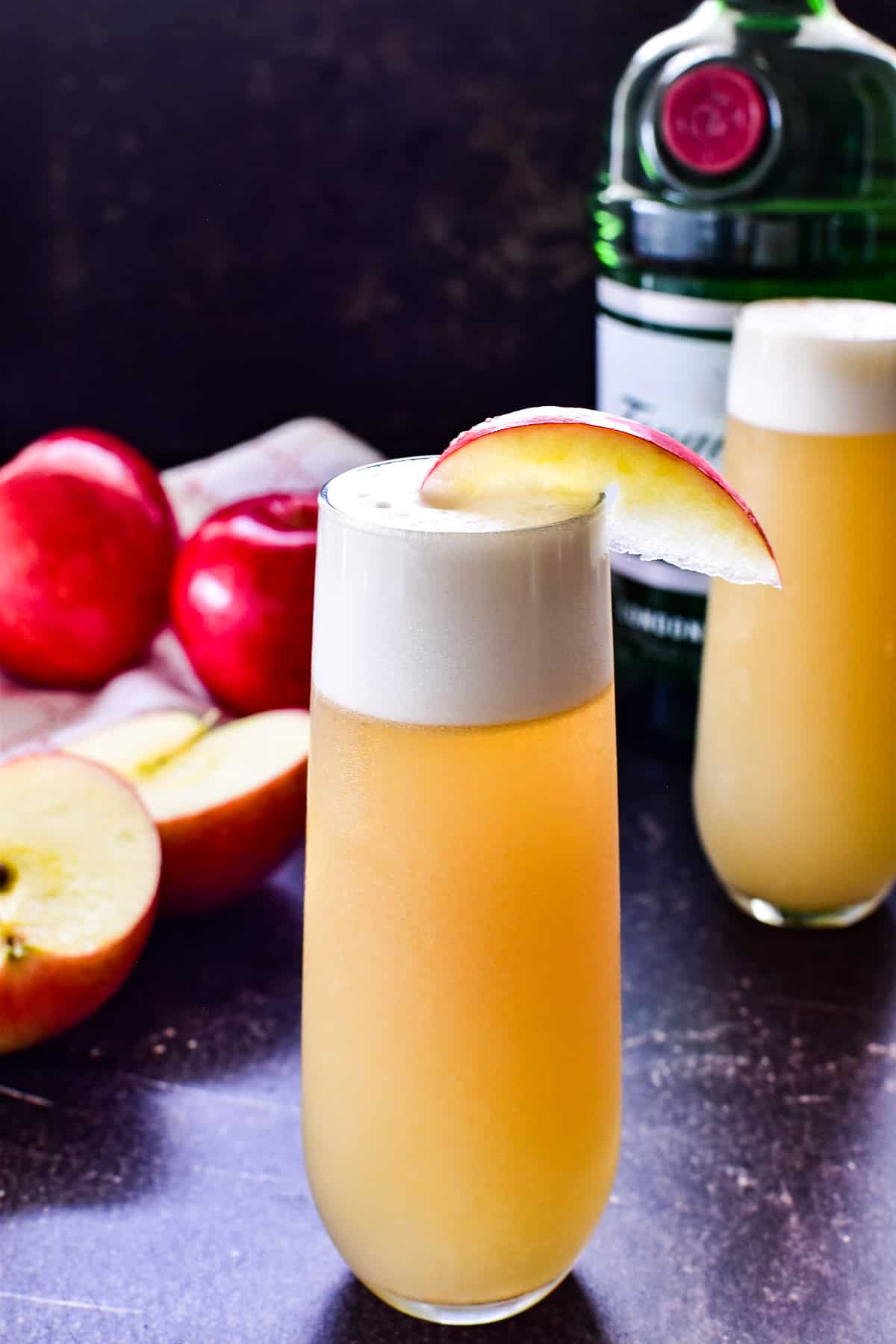 Apple Gin Fizz in a glass with a bottle of Tanqueray and fresh red apples