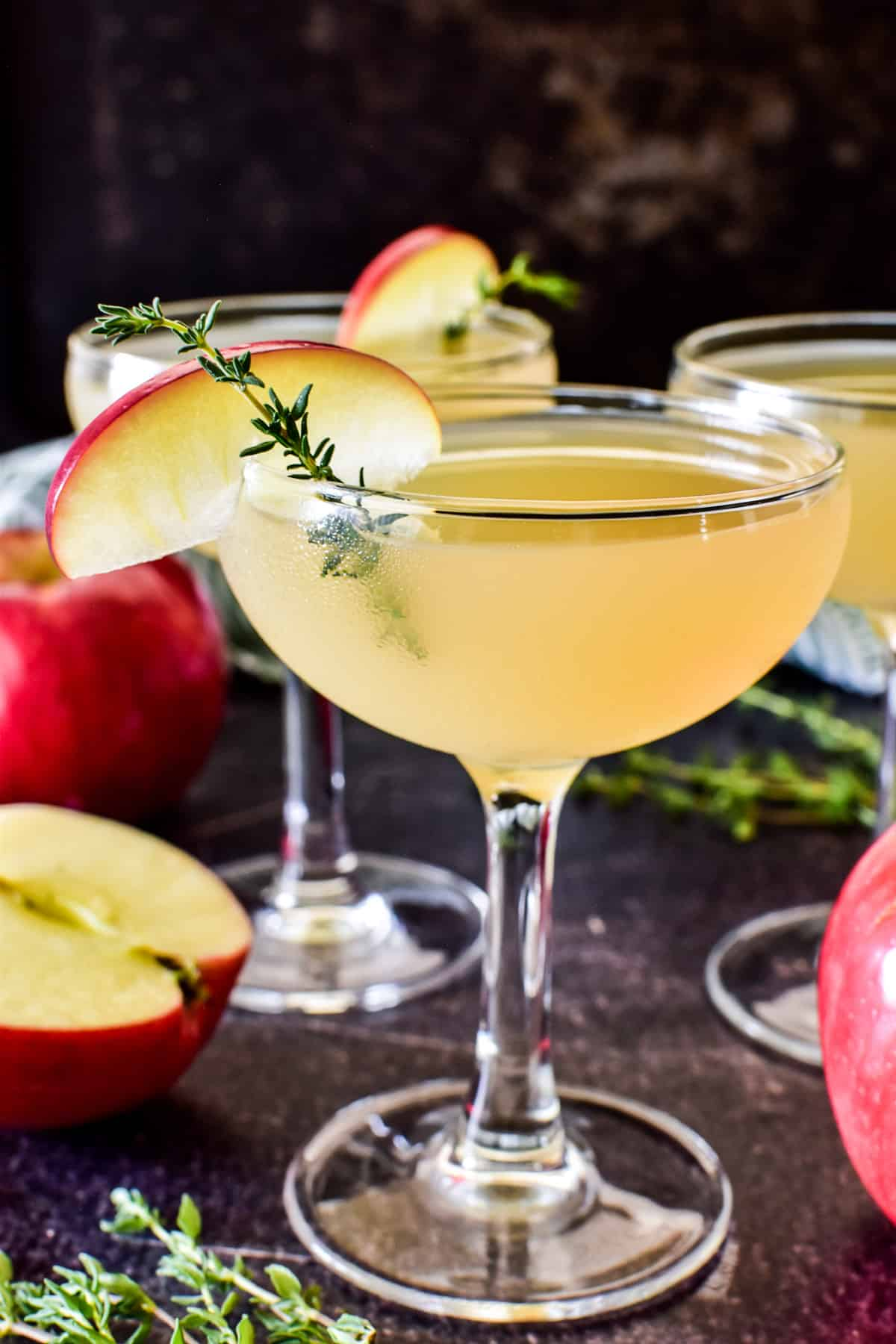 Close up of Appletini in a coupe glass garnished with apple and thyme