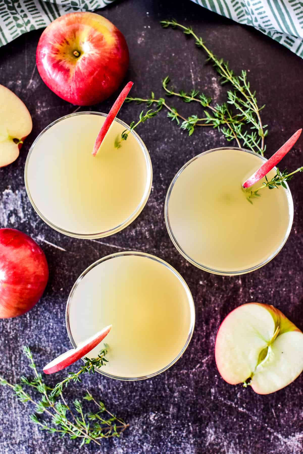 Overhead shot of 3 appletinis with fresh apples and thyme in the background