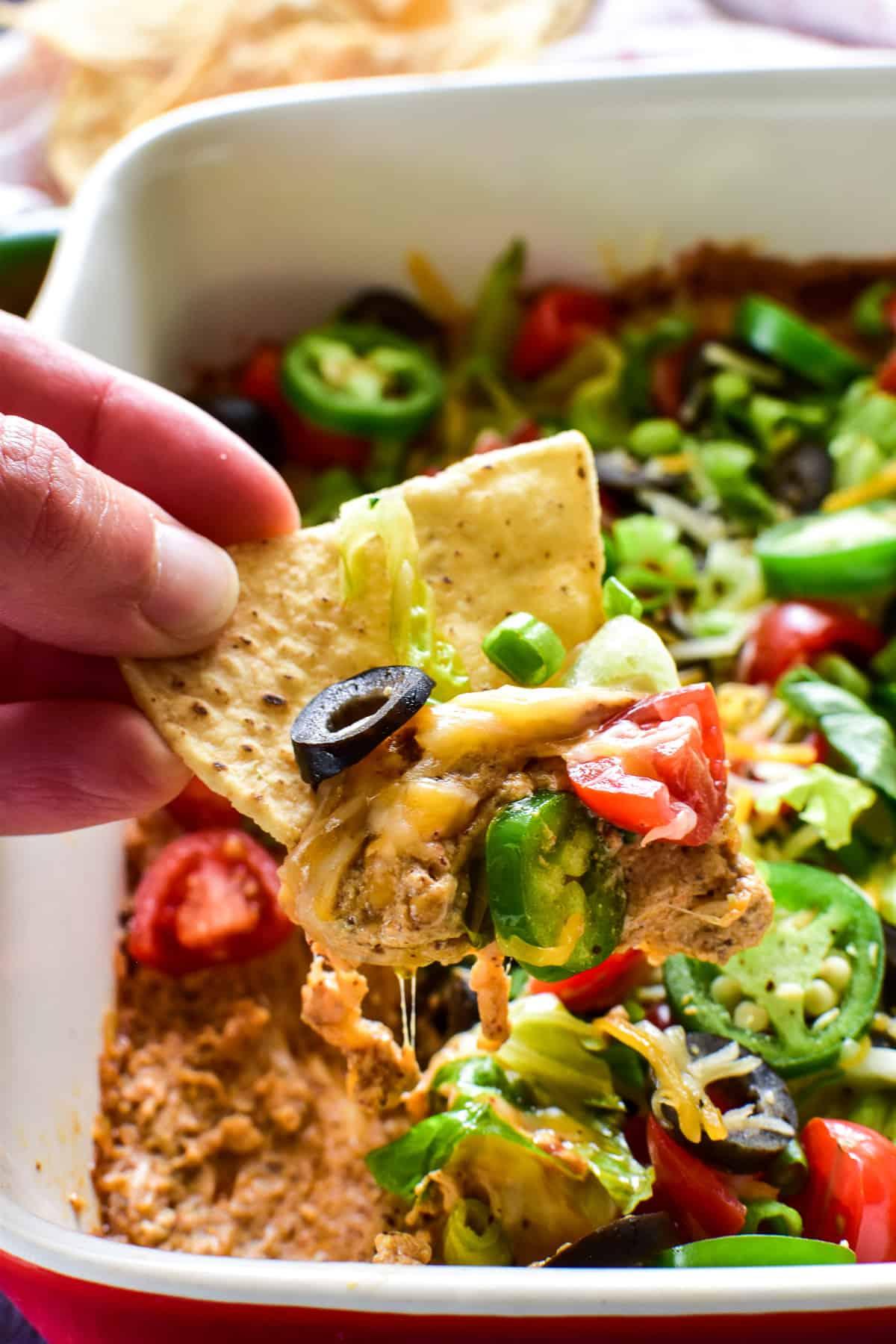 Tortilla chip dipping into Baked Taco Dip