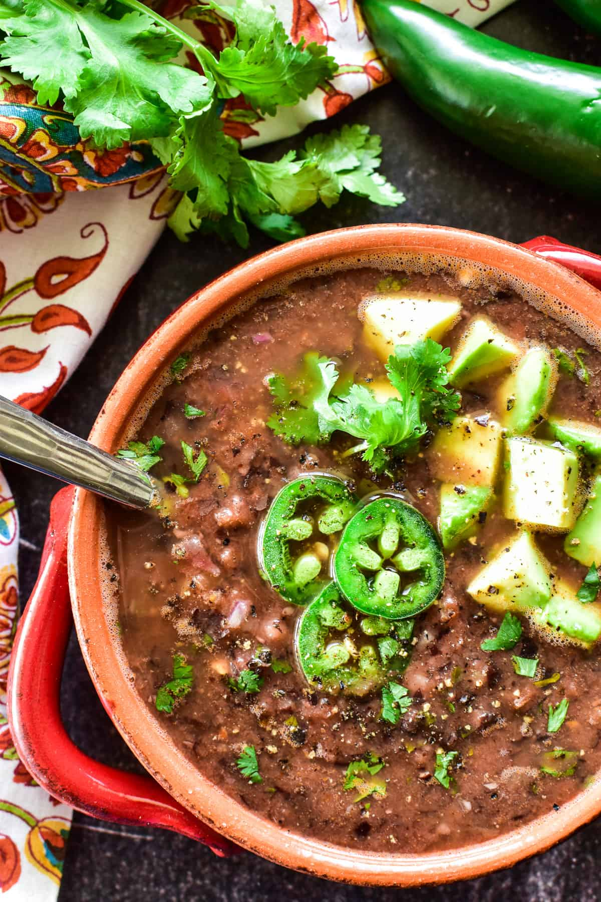 Overhead shot of Black Bean Soup in a red & orange bowl with fresh jalapenos and avocado