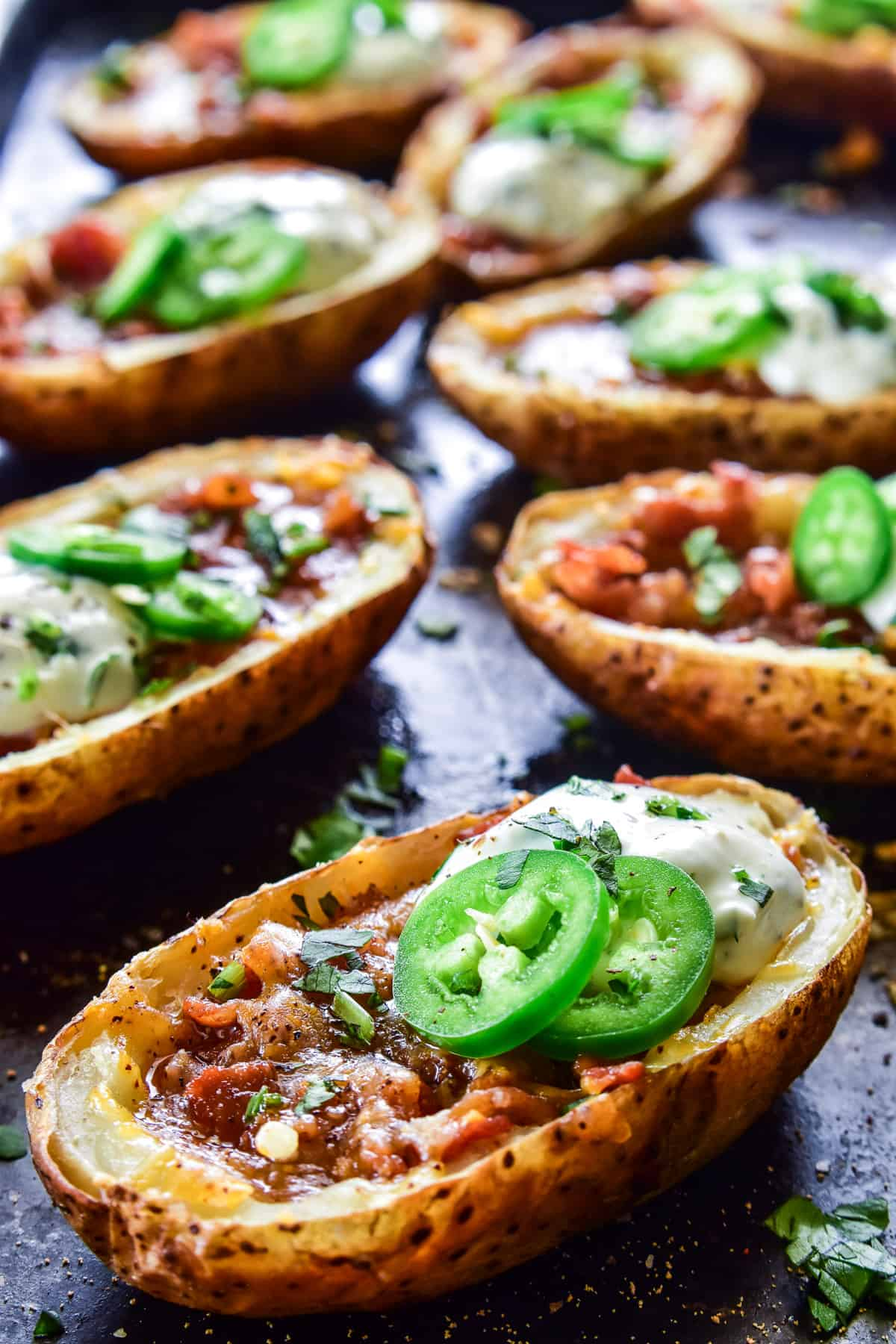 Close up of Loaded Potato Skins with jalapeños and cilantro lime sauce