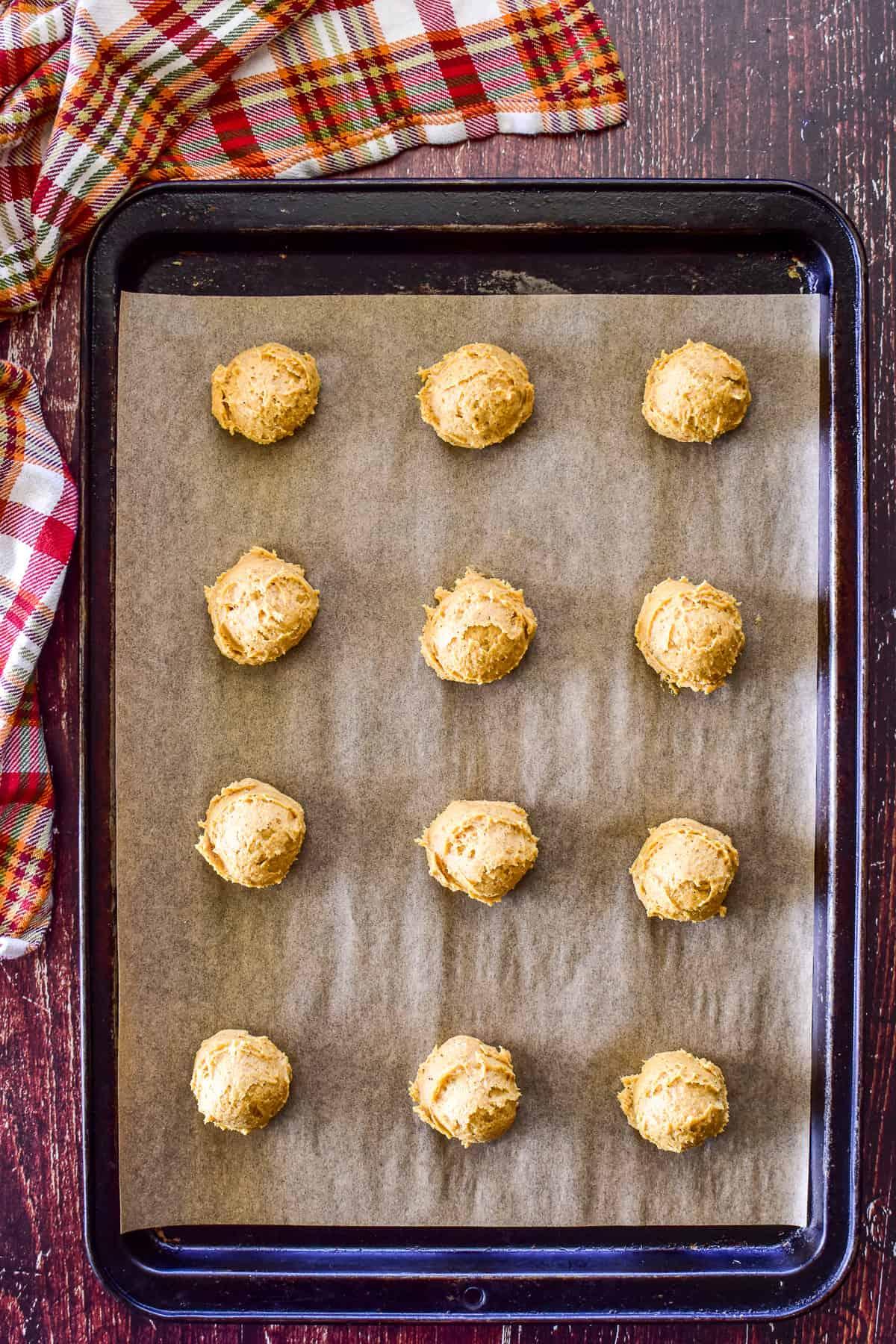 Overhead shot of pumpkin cookie dough scooped onto a baking sheet