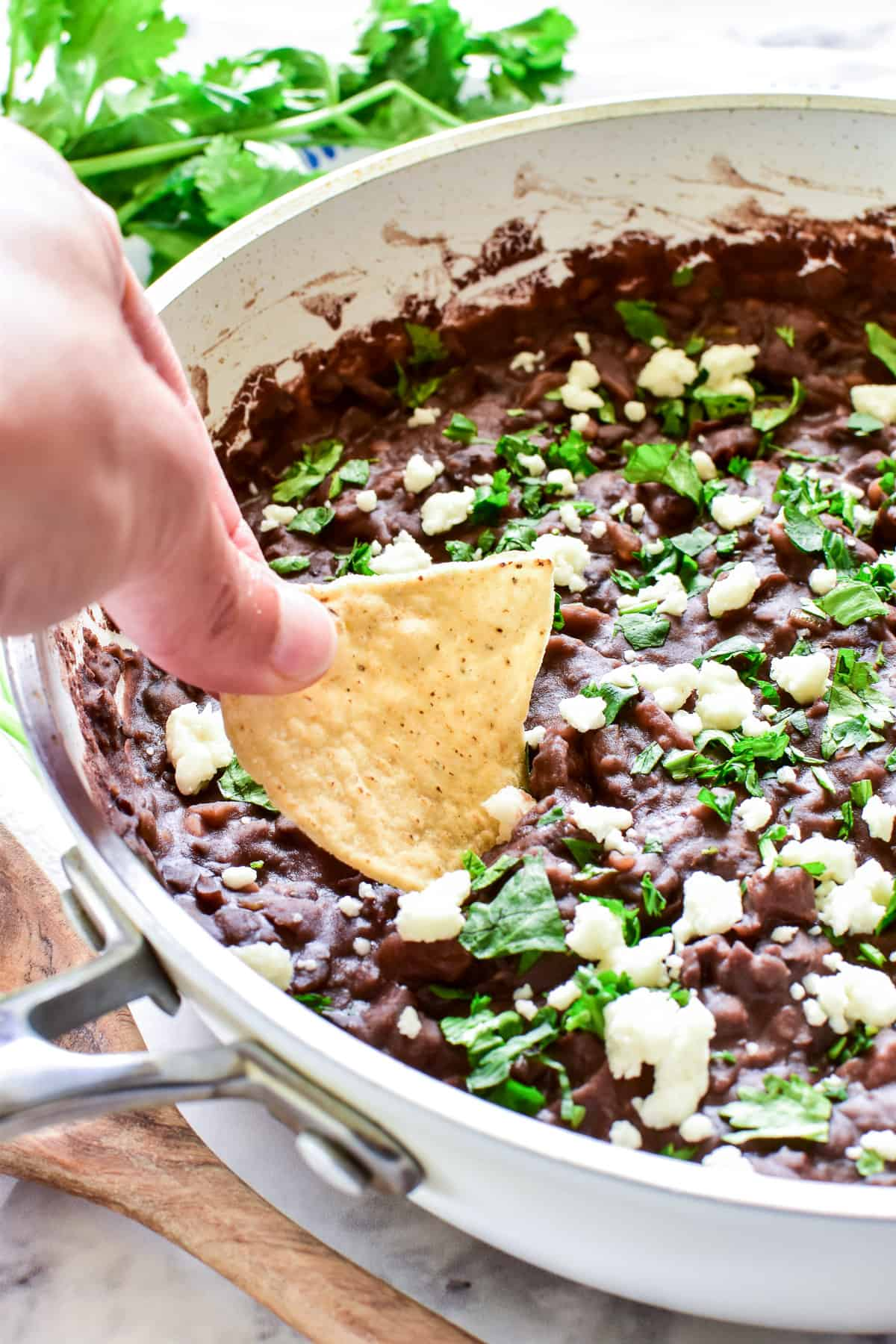 Dipping a chip into Refried Black Beans