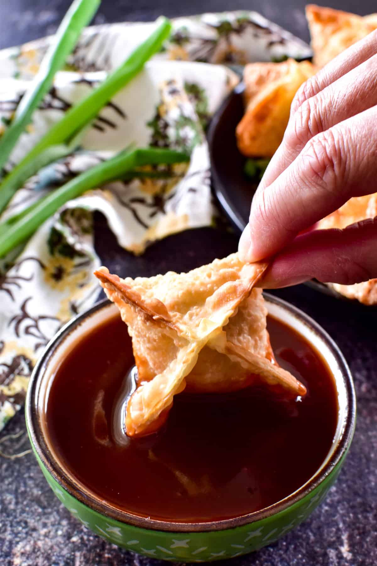 Crab Rangoon being dipped into sweet & sour sauce