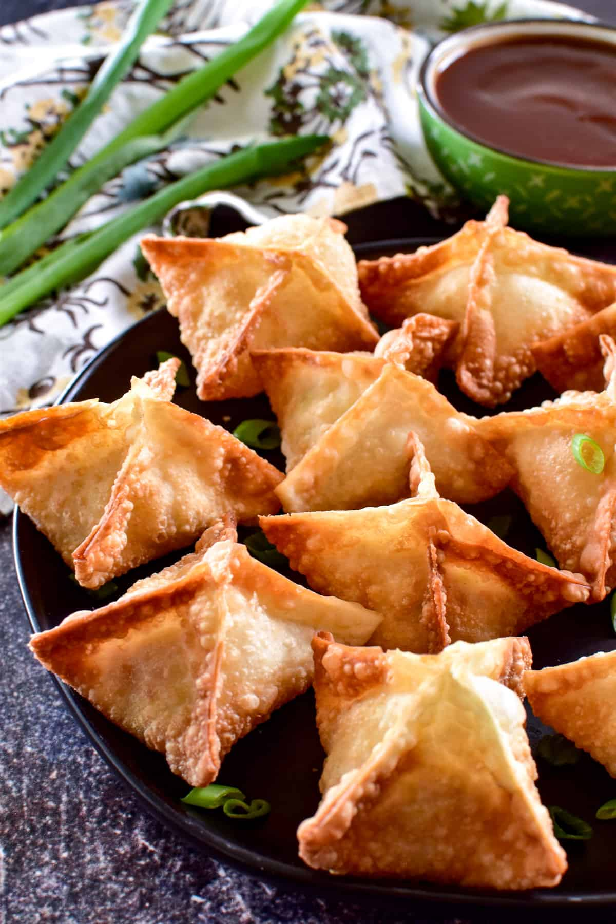 Side view of Crab Rangoon with green onions and sweet & sour sauce