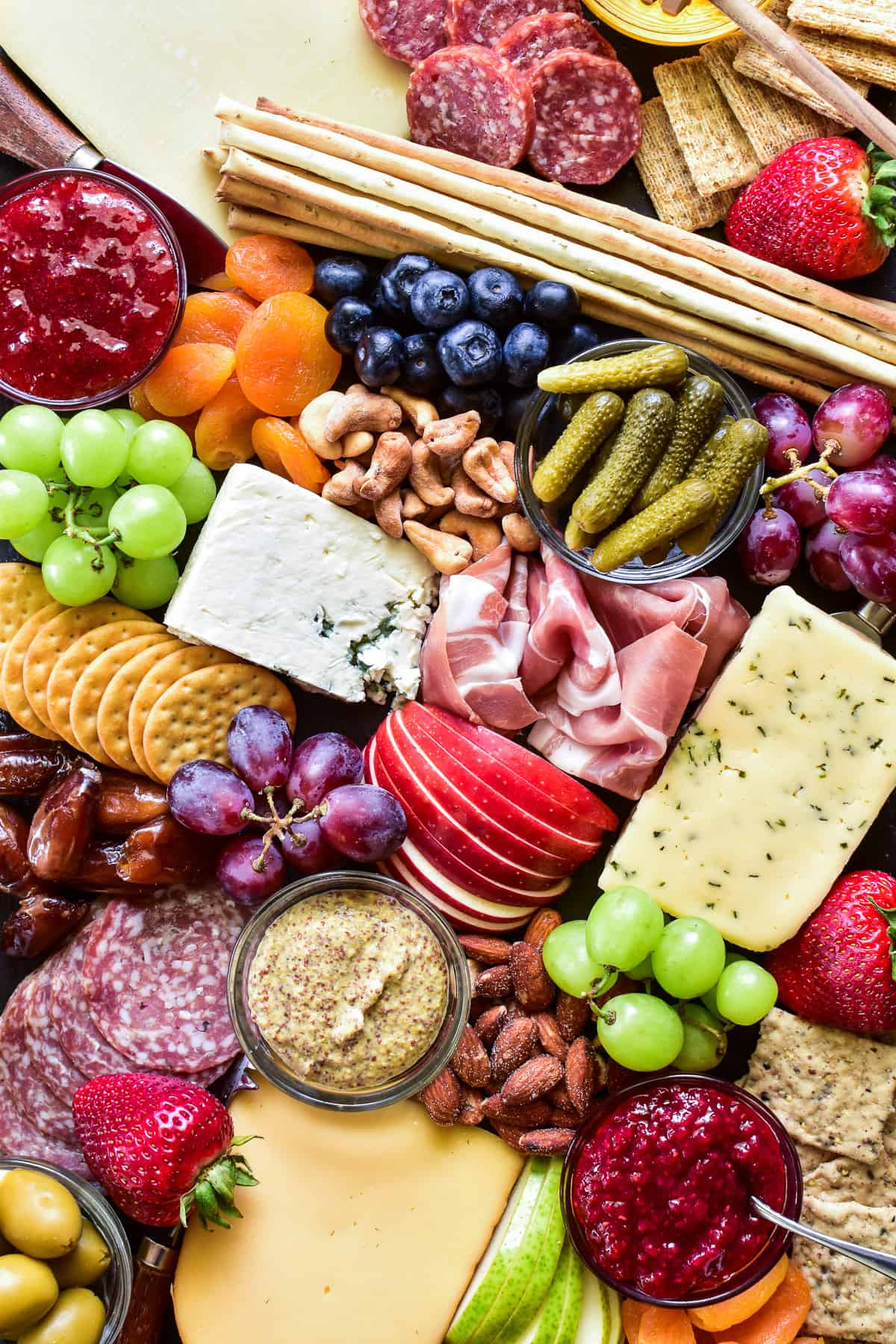Overhead shot of meats, cheeses, crackers, fruits, nuts, and condiments on a charcuterie board