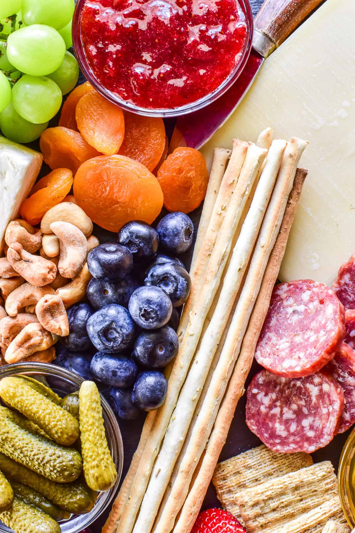 Close up of blueberries, dried apricots, cashews, cheese, salami, and breadsticks