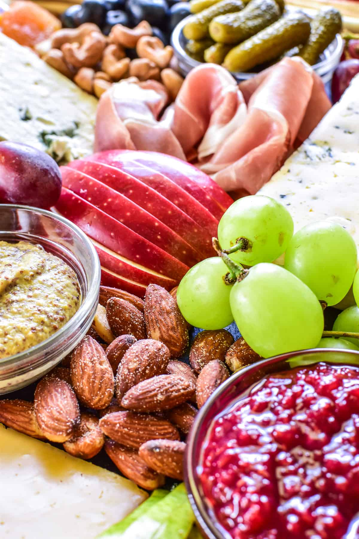 Close up of grapes, apples, almonds, and more on a charcuterie board