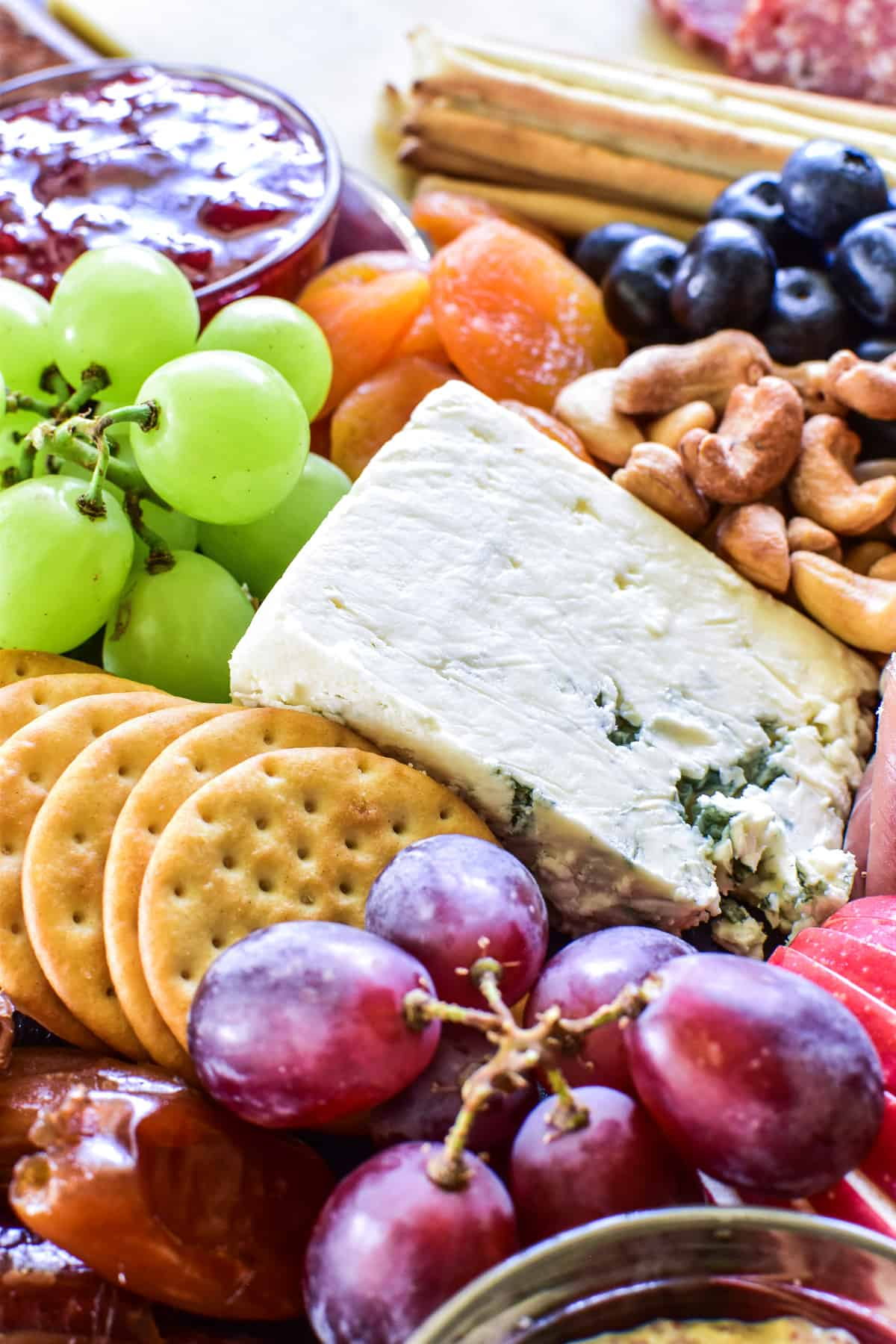 Close up of grapes, cheese, crackers, and more on a charcuterie board