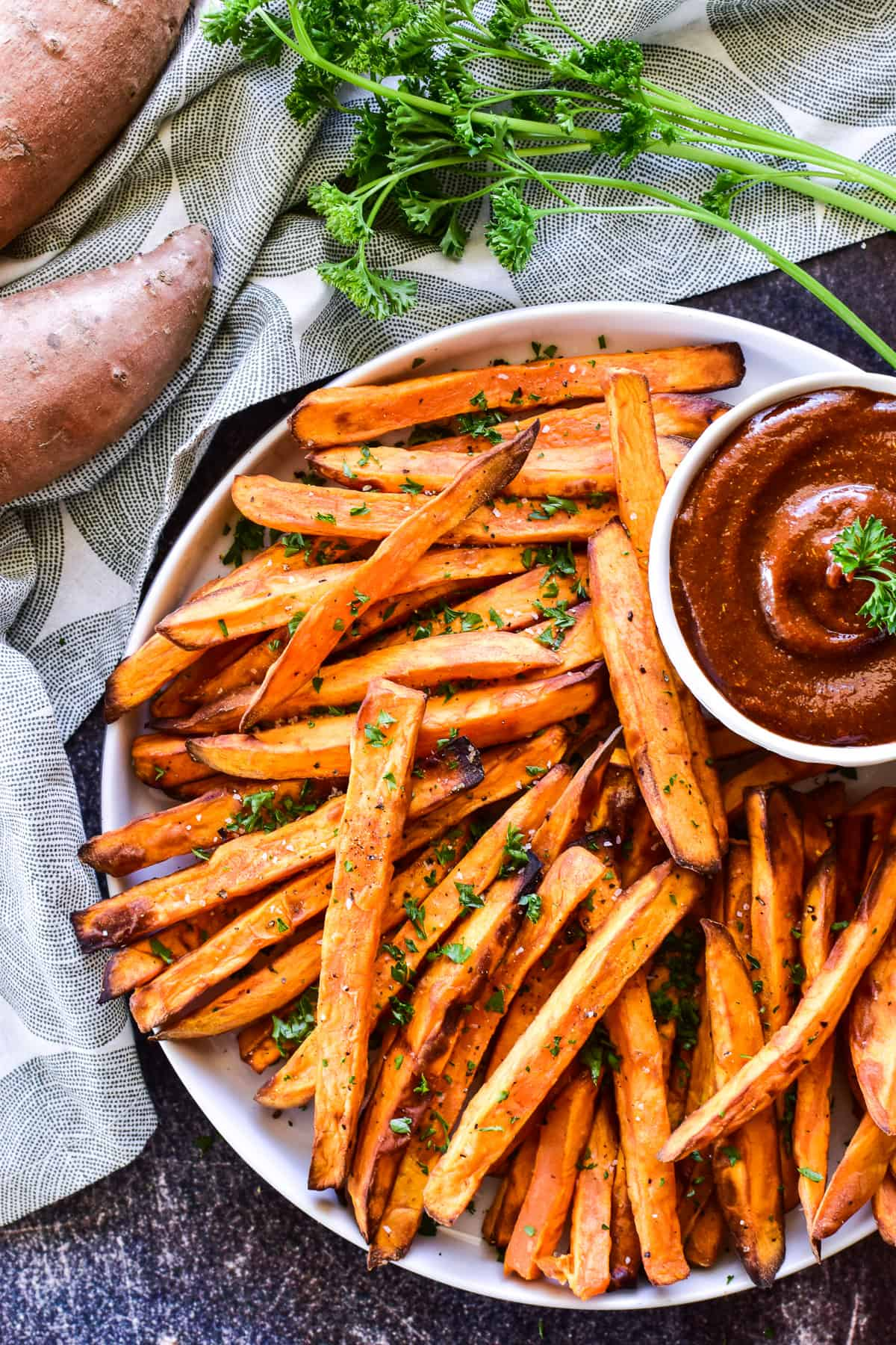 Overhead shot of Sweet Potato Fries on a white plate with fresh parsley and curry ketchup