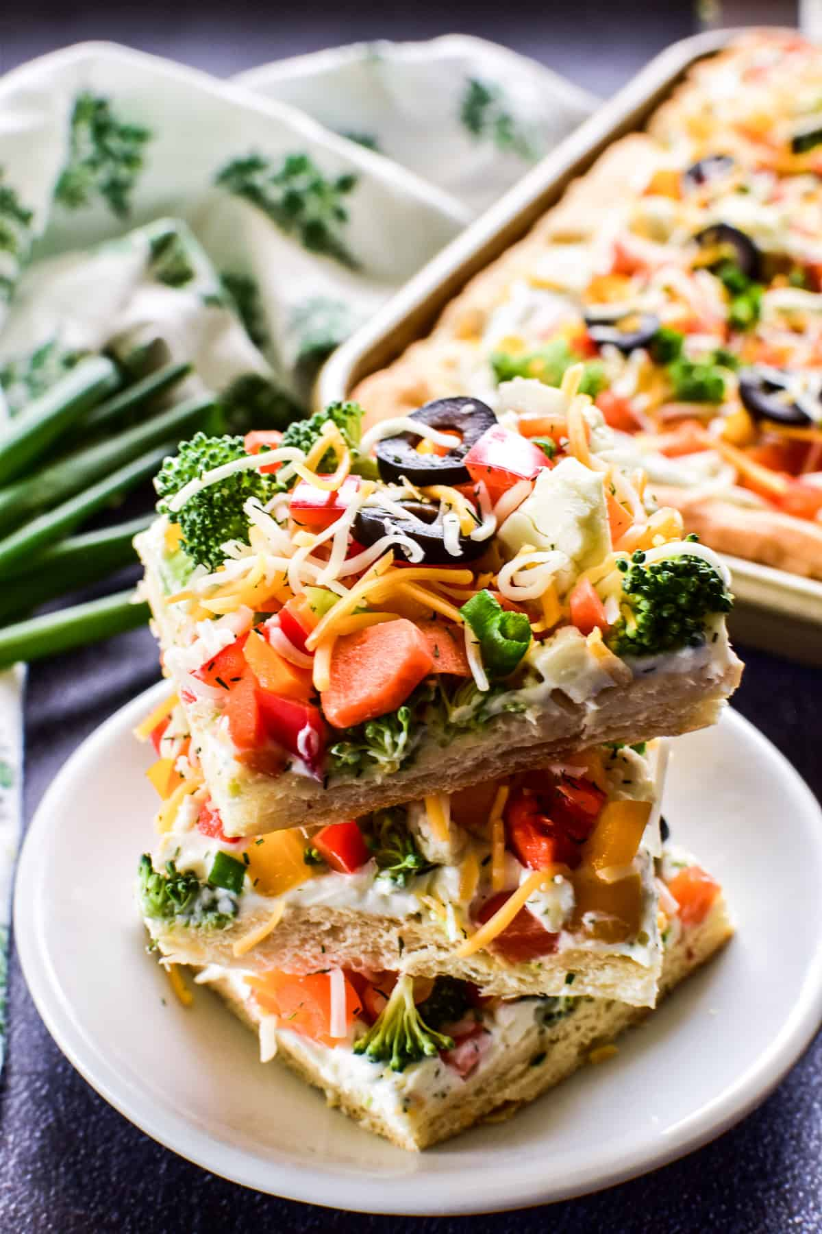 3 squares of Crescent Roll Veggie Pizza stacked on a plate