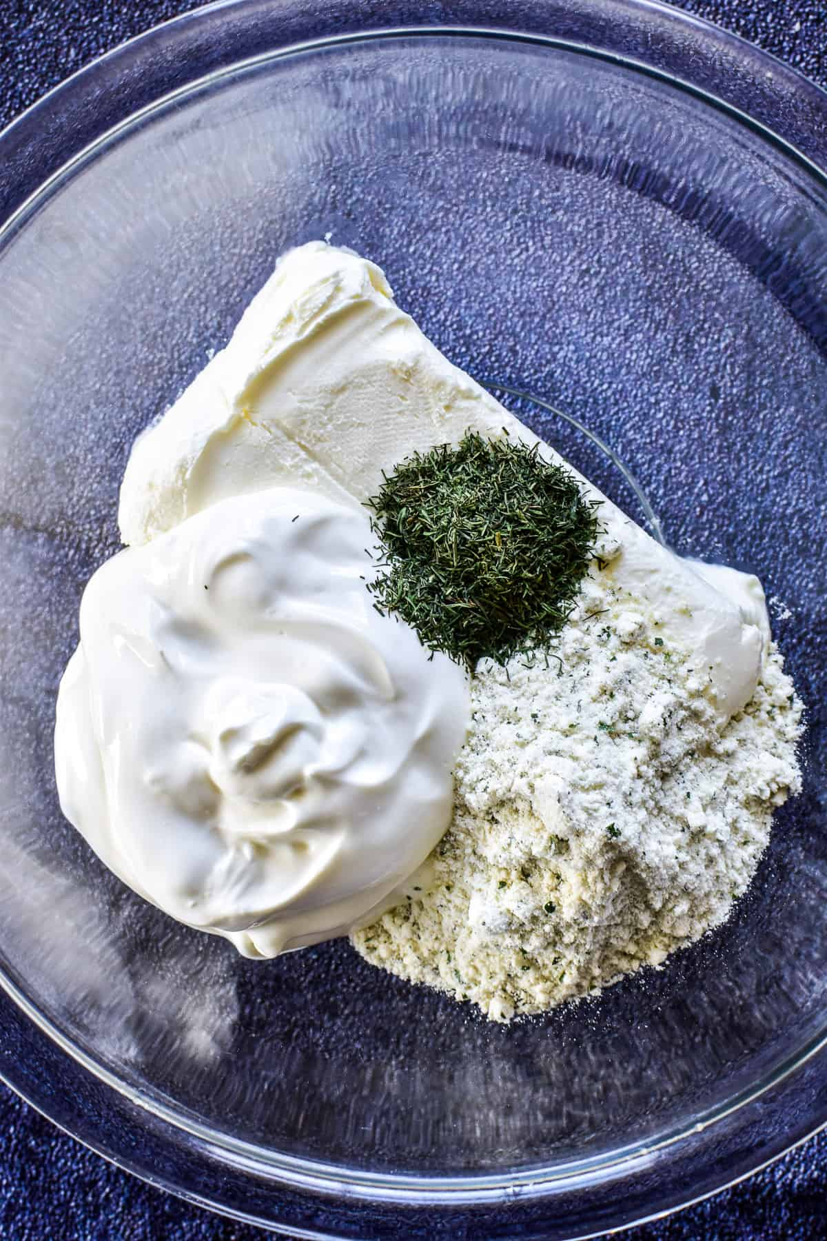 Cream cheese, sour cream, ranch dressing mix, and dill weed in a mixing bowl