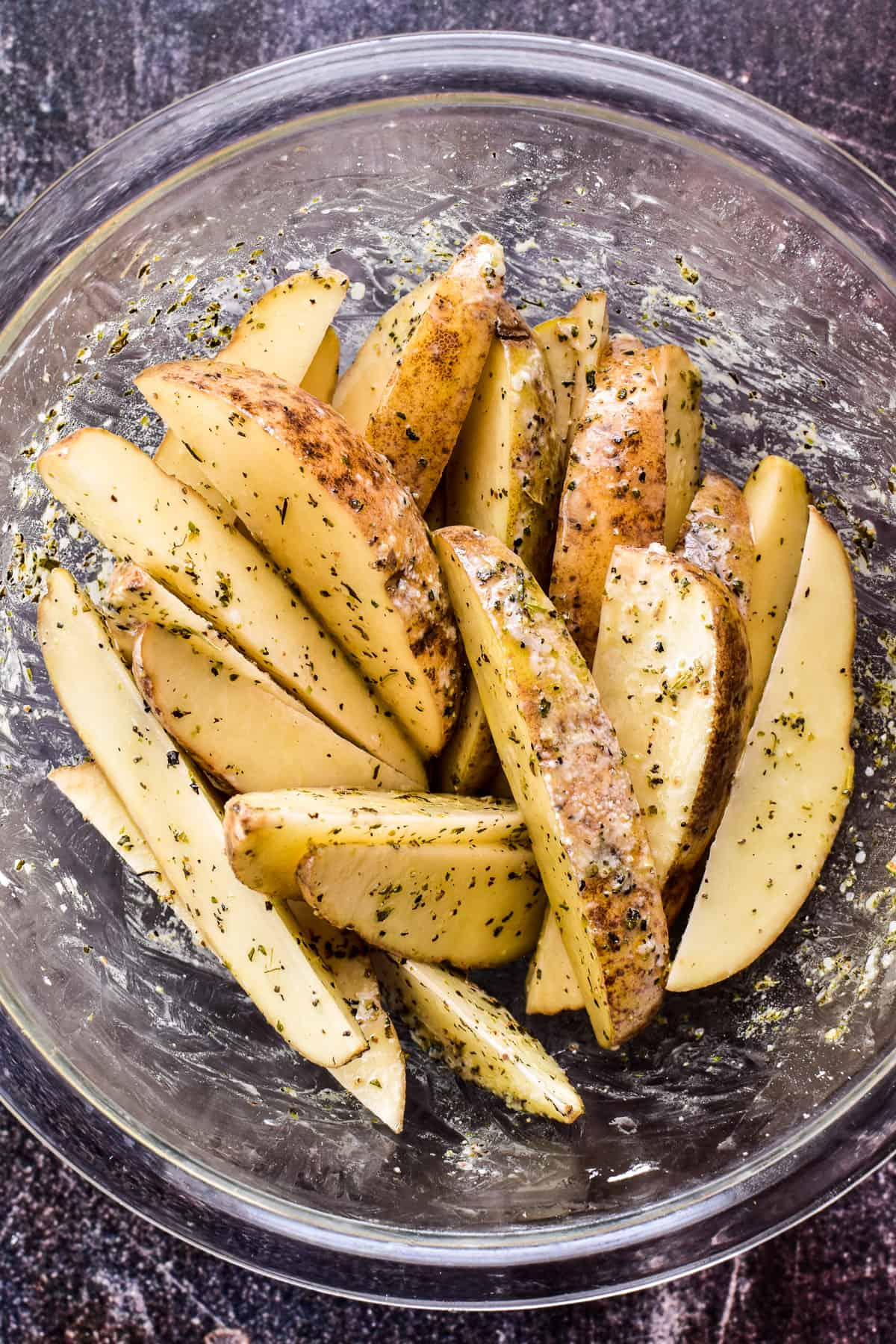 Potato Wedges combined with oil, seasonings, and cornstarch in a glass mixing bowl