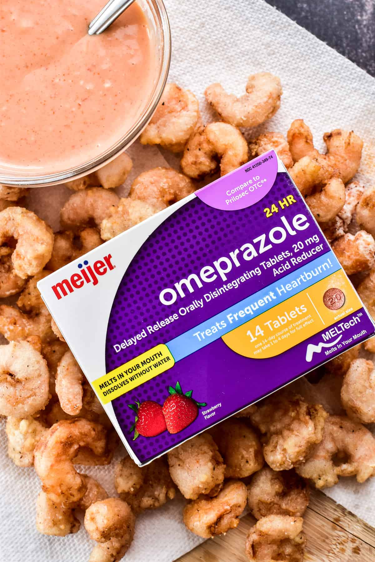 Close up of fried shrimp with a box of Meijer Omeprazole ODT