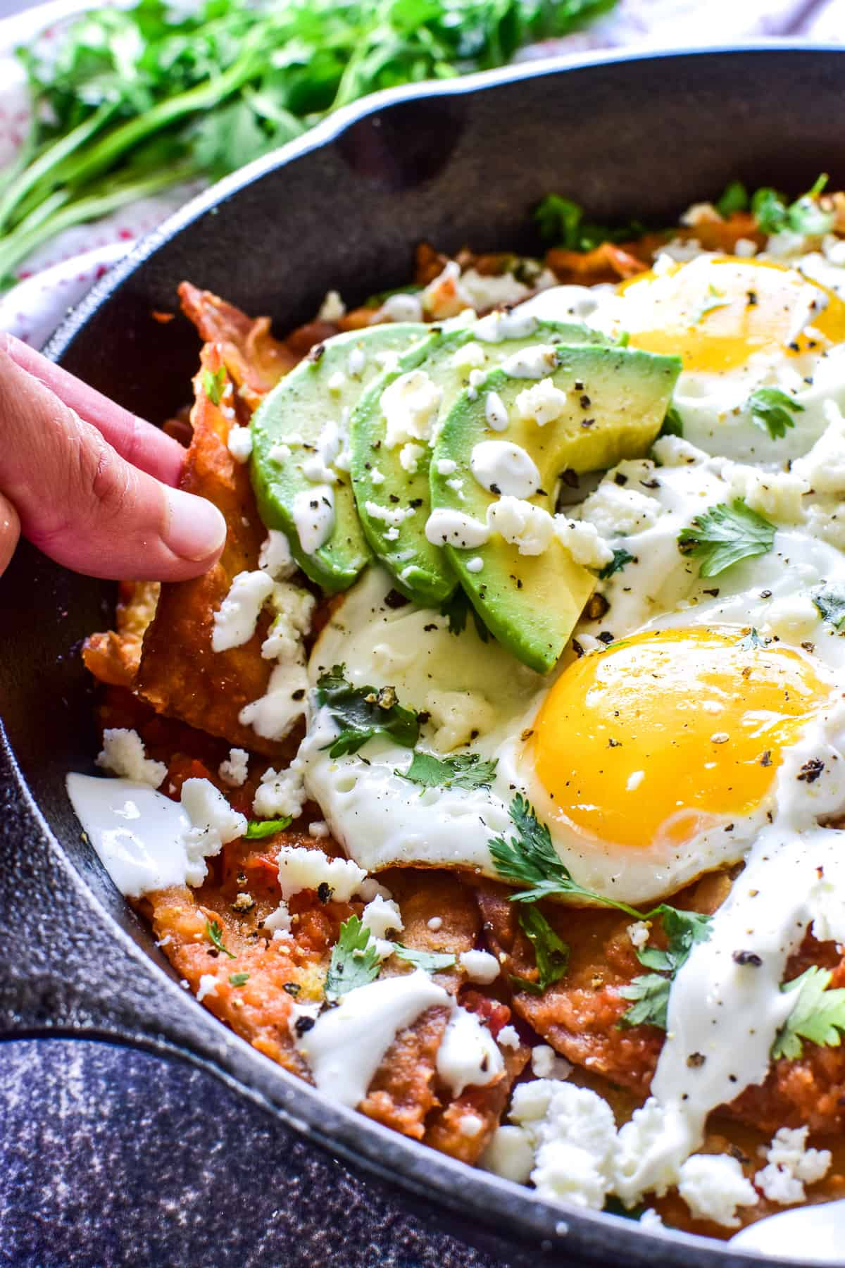 Photo of fingers grabbing chilaquiles