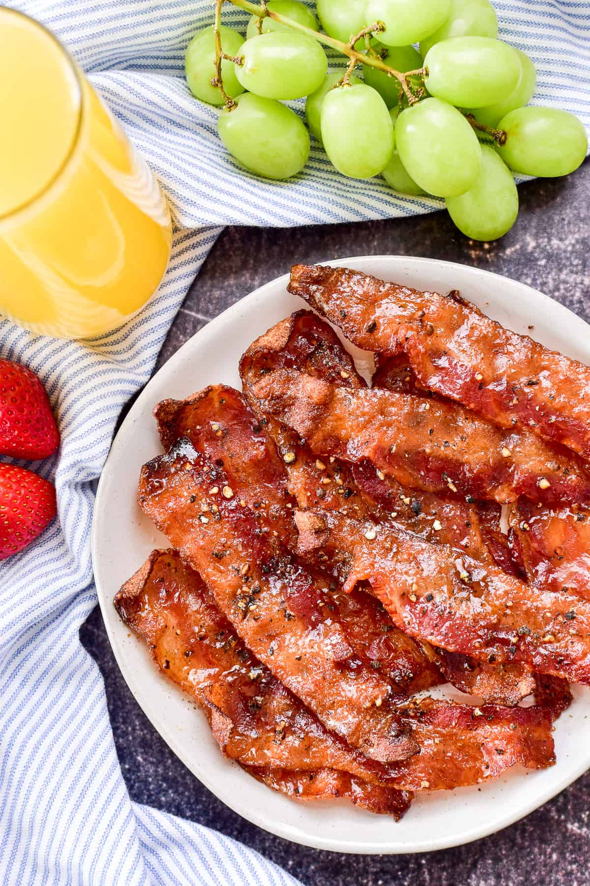 Candied Bacon on a white plate with fruit & orange juice