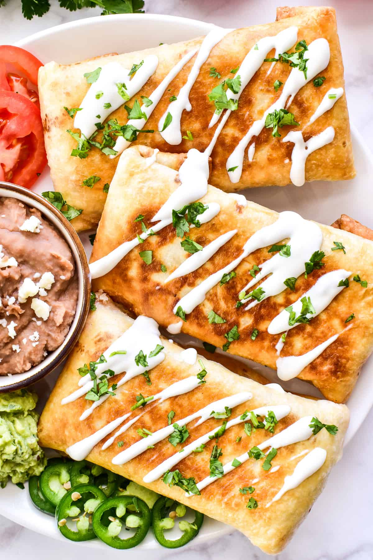 Overhead close up of chimichangas with crema and cilantro