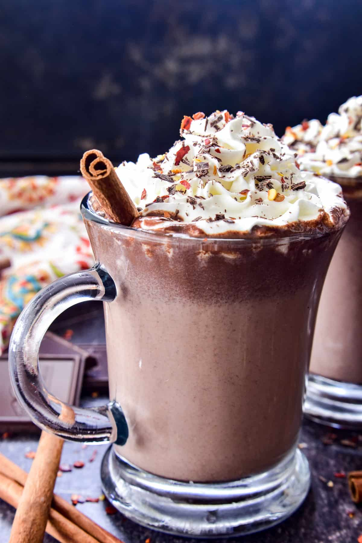 Mexican Hot Chocolate in a glass mug with whipped cream and garnishes