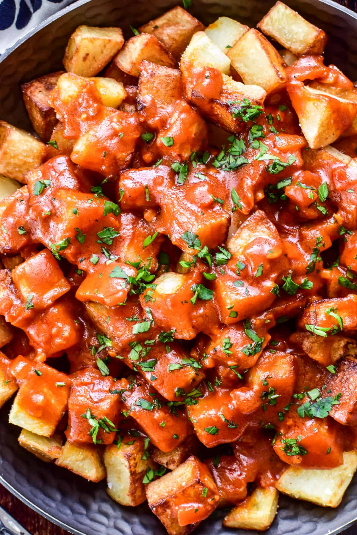 Close up of Patatas Bravas with minced parsley