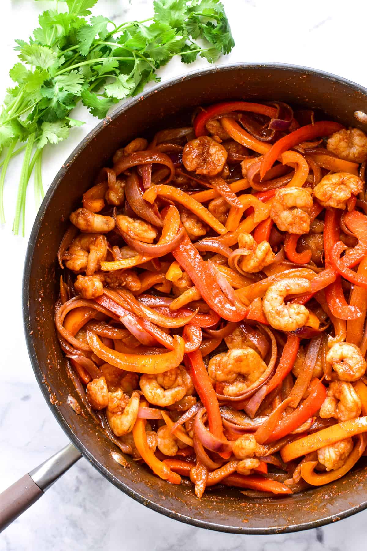 Fajita peppers, onions, and shrimp in a skillet with seasoning