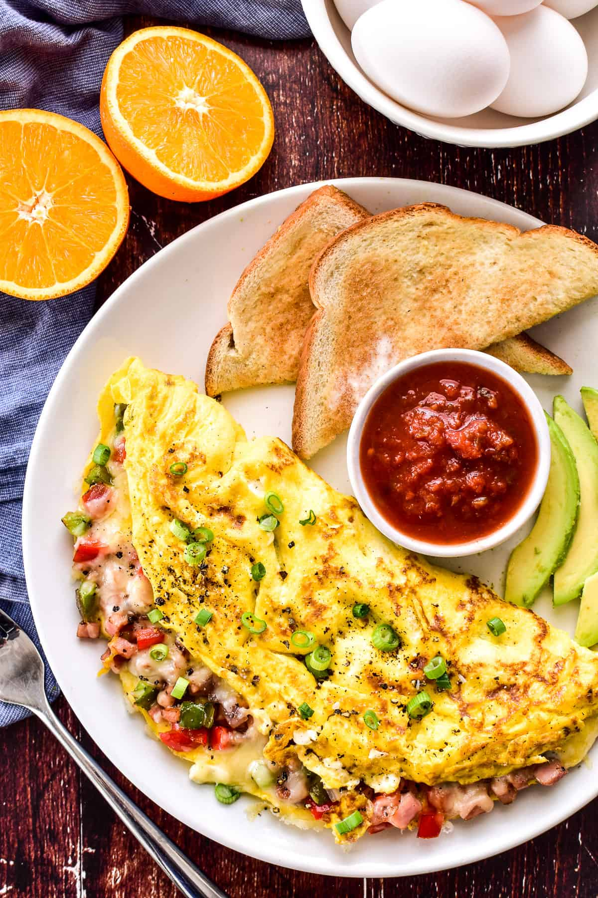 Western Omelette on a plate with salsa, avocado slices, and toast