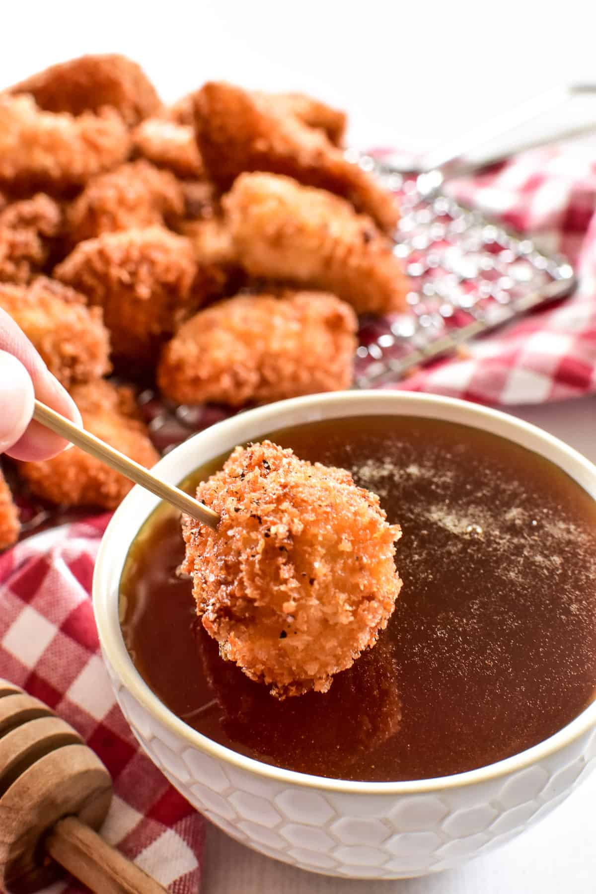 Crispy Chicken Nugget being dipped into Hot Honey