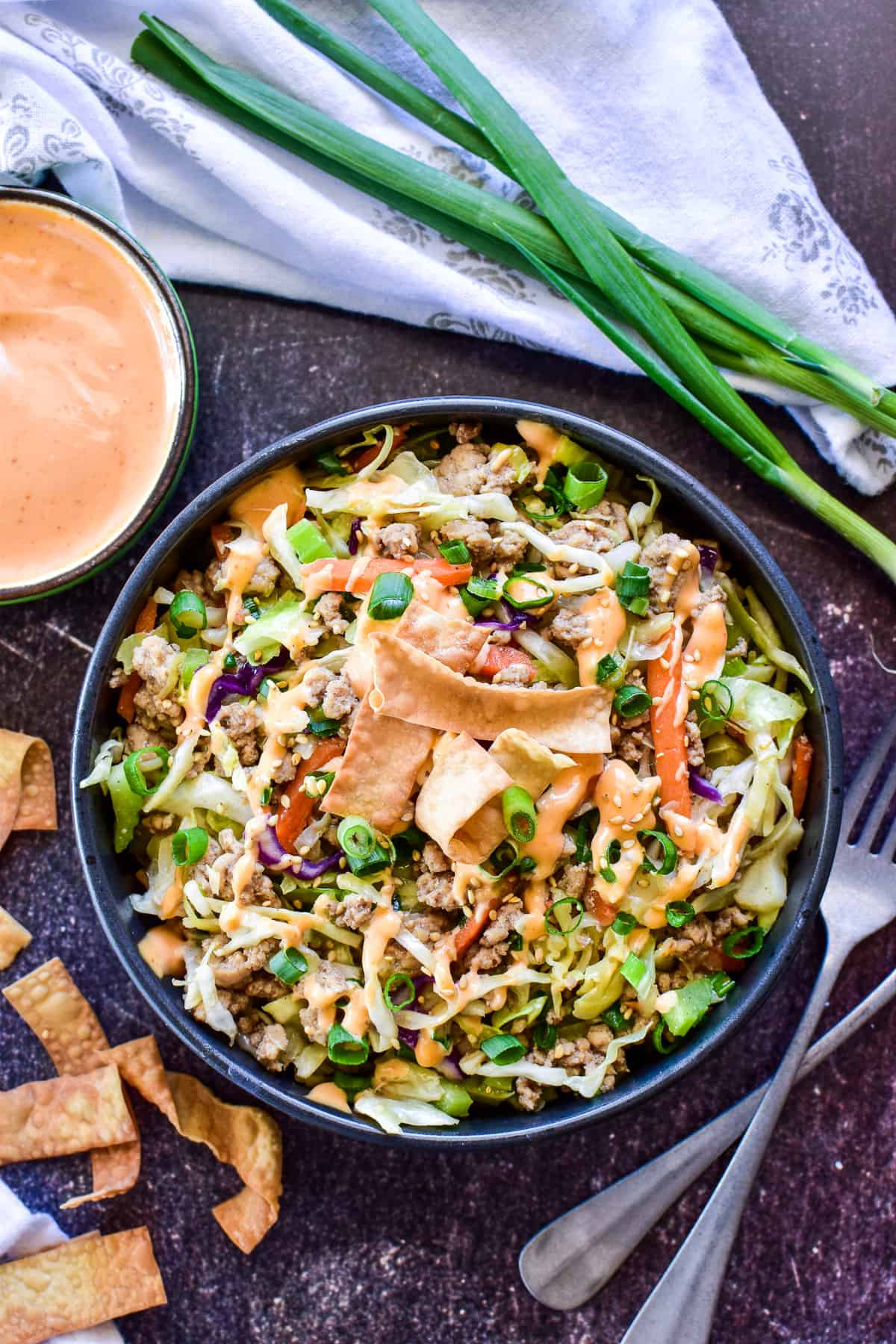 Egg Roll in a Bowl plated with spicy mayo and green onions