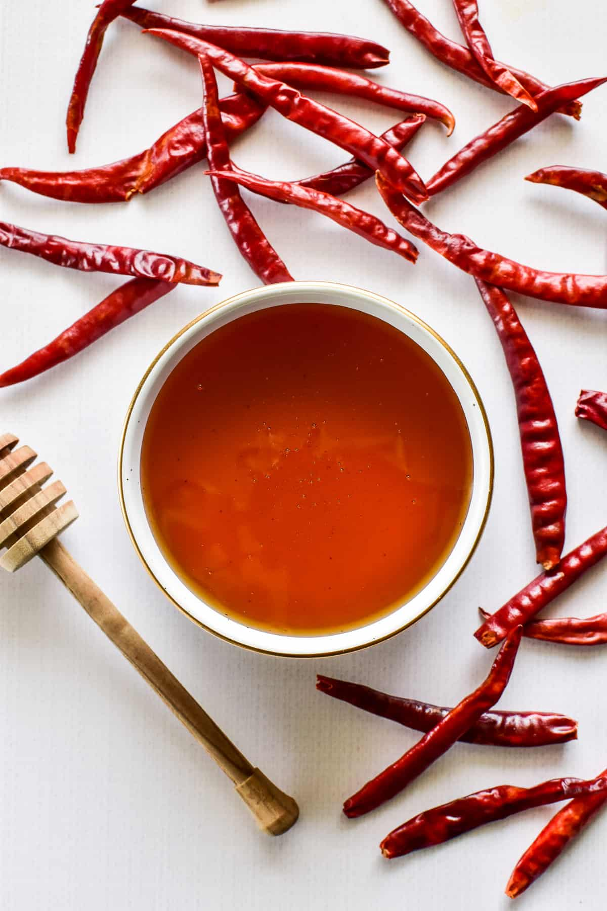 A bowl of honey surrounded by hot chili peppers