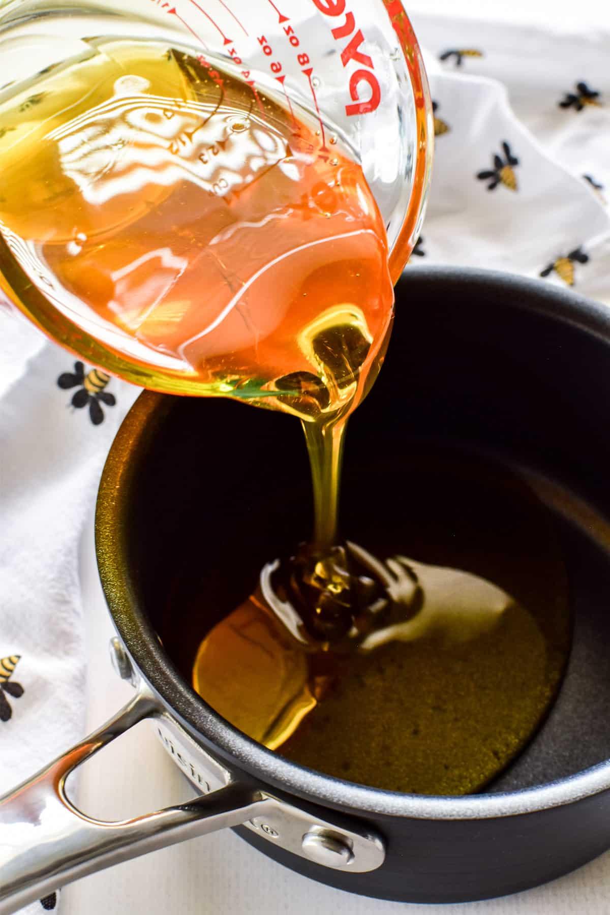 Honey pouring into a saucepan