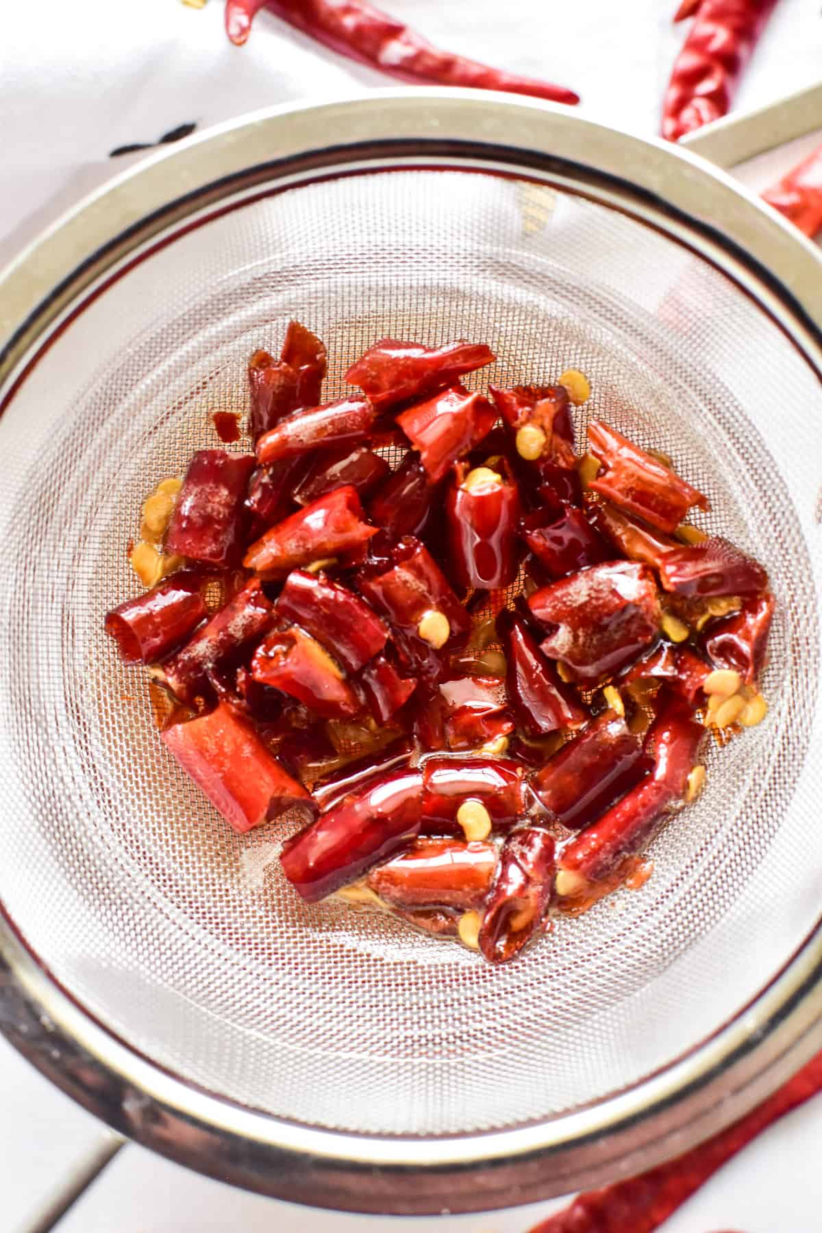 Overhead image of chopped chili peppers being strained from hot honey