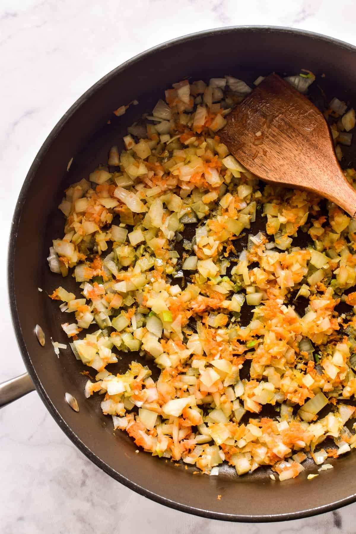 Sautéed onions, garlic, and shredded carrots in a saucepan