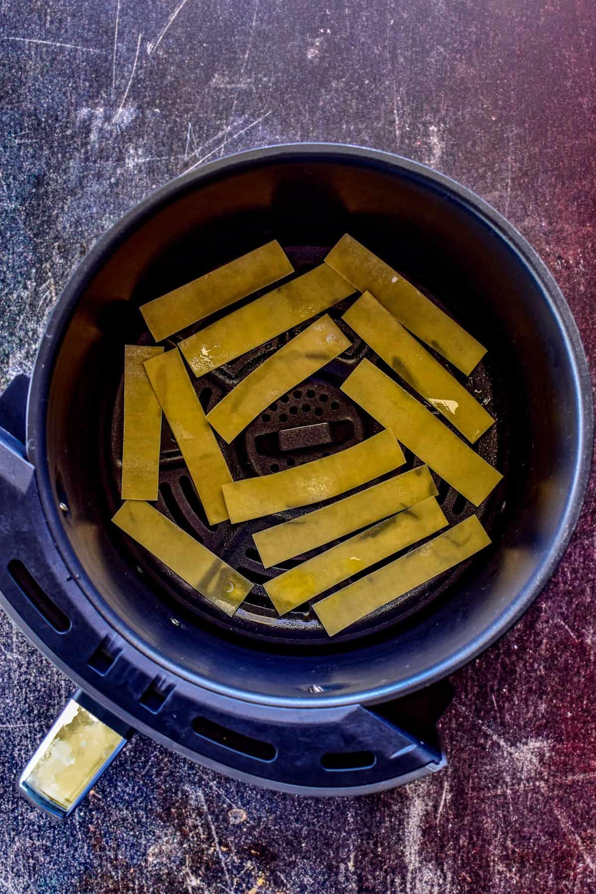 Wonton strips in an air fryer basket