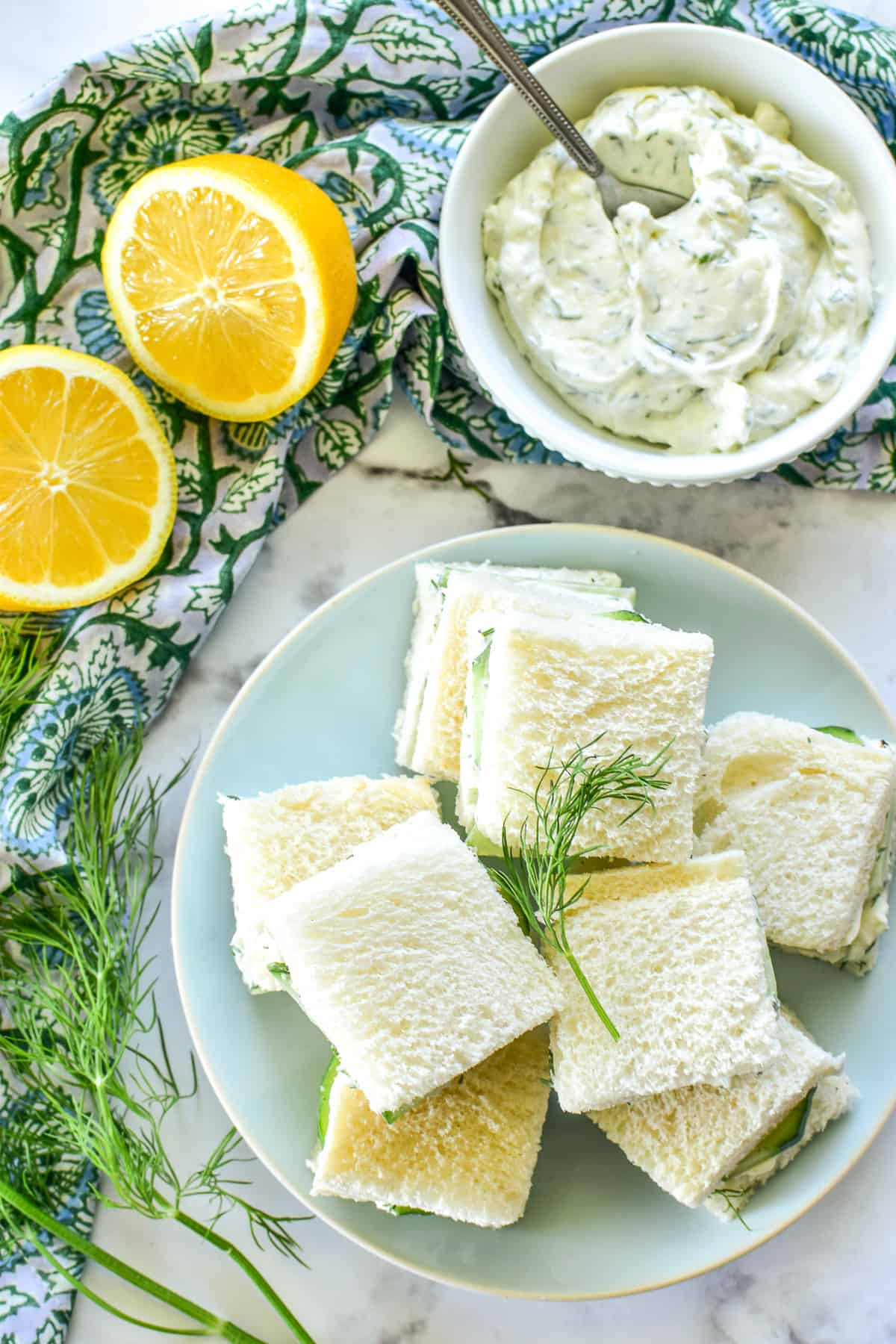Overhead image of Cucumber Sandwiches on a light blue plate with fresh lemons