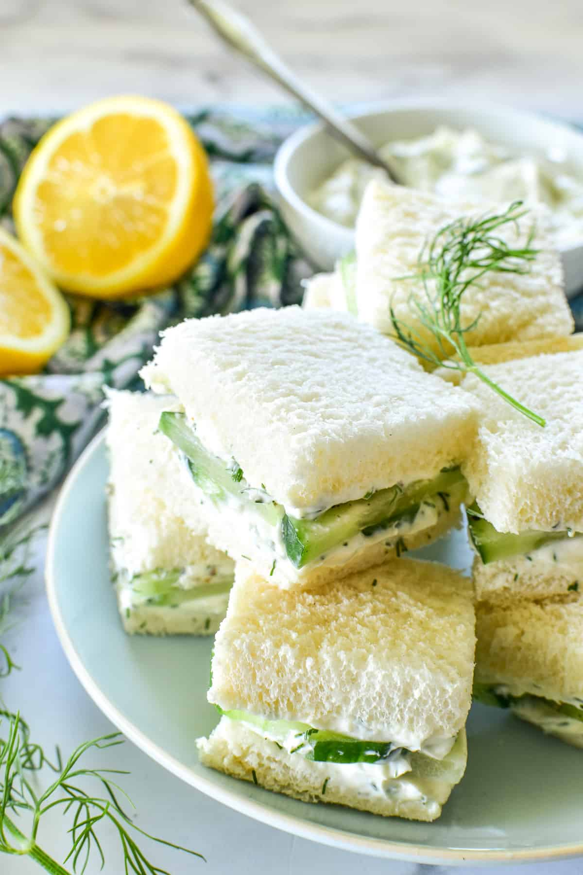 Cucumber Sandwiches cut in squares on a light blue plate