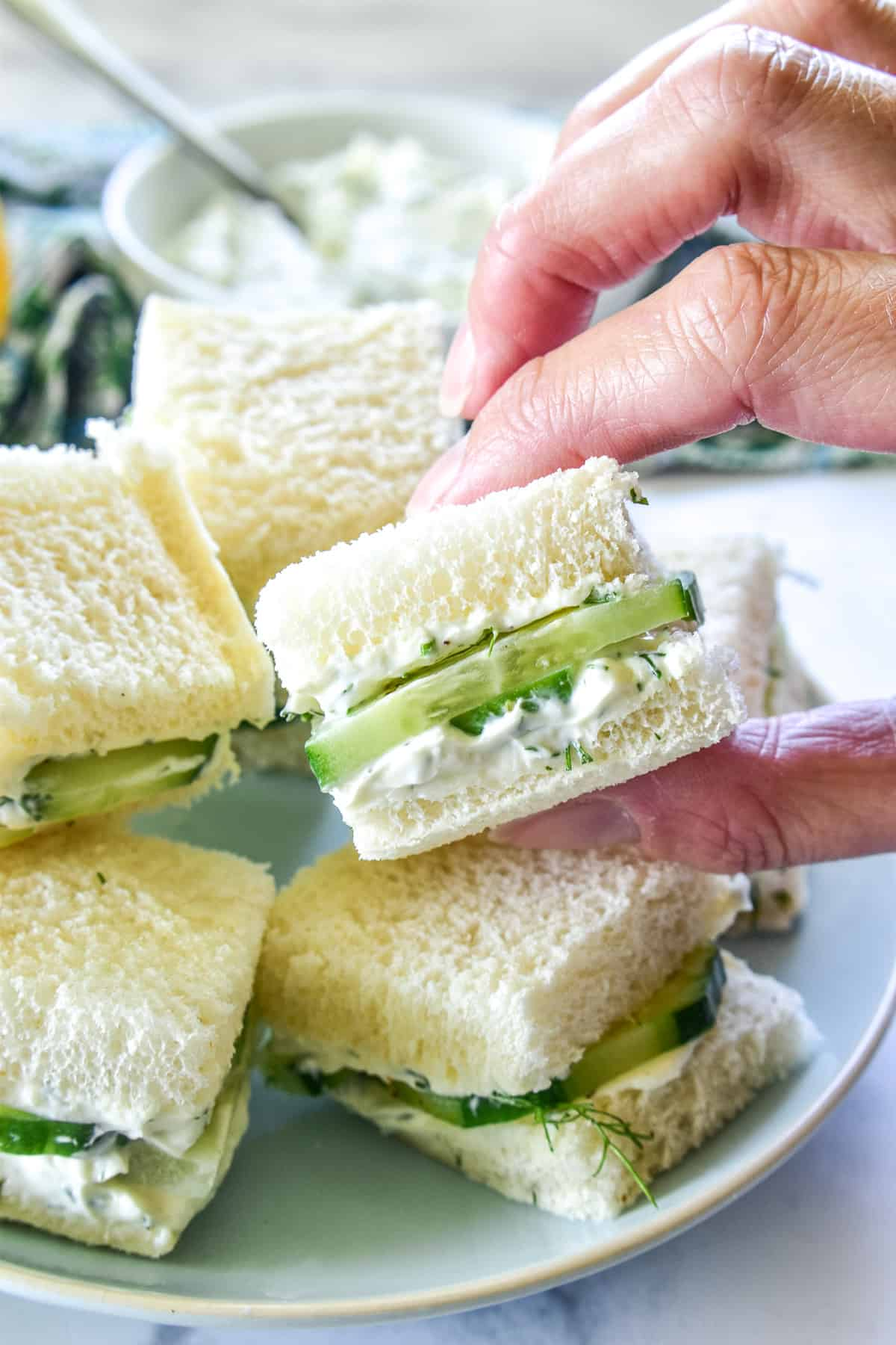 Hand grabbing a Cucumber Sandwich square