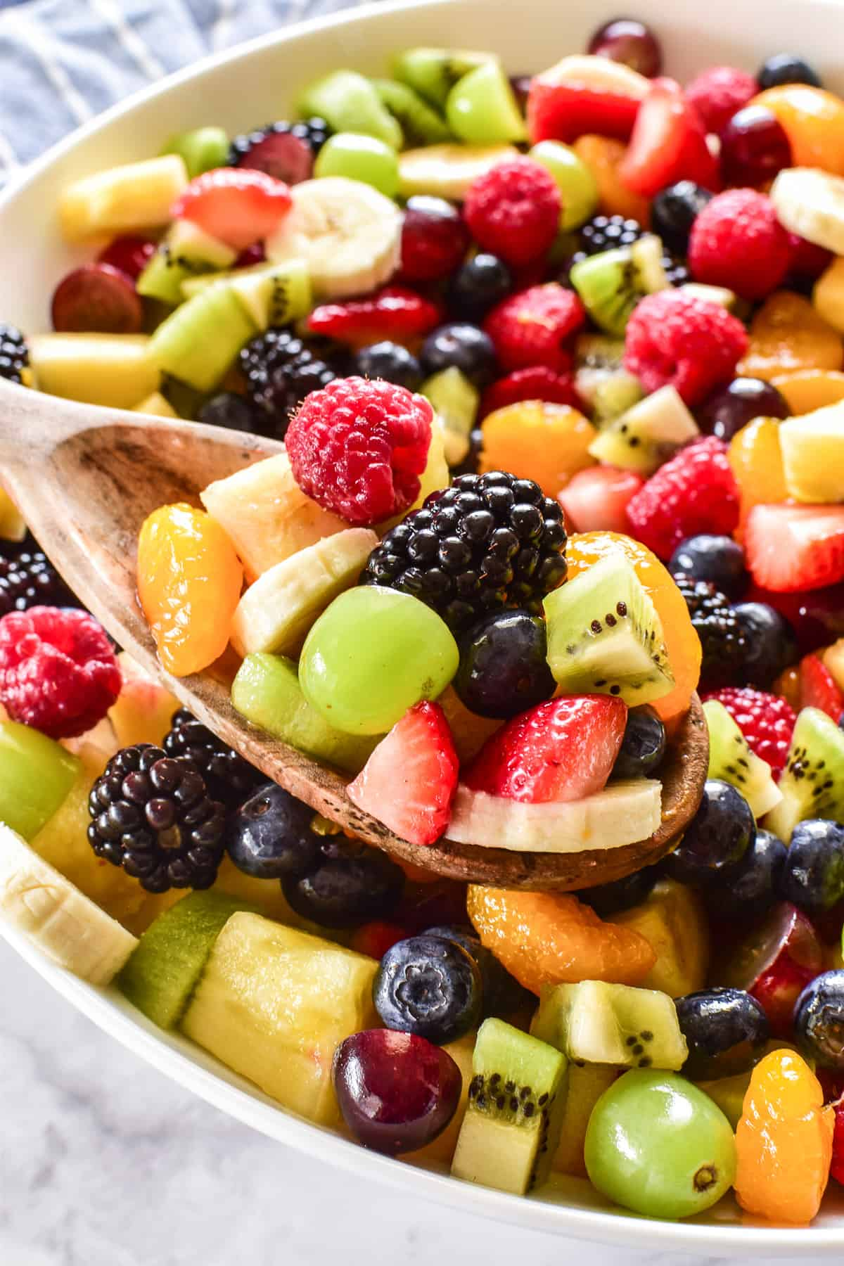 Close up of Fruit Salad on a wooden serving spoon