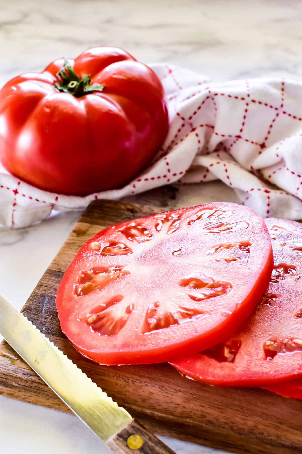 Tomatoes sliced on a wooden cutting board