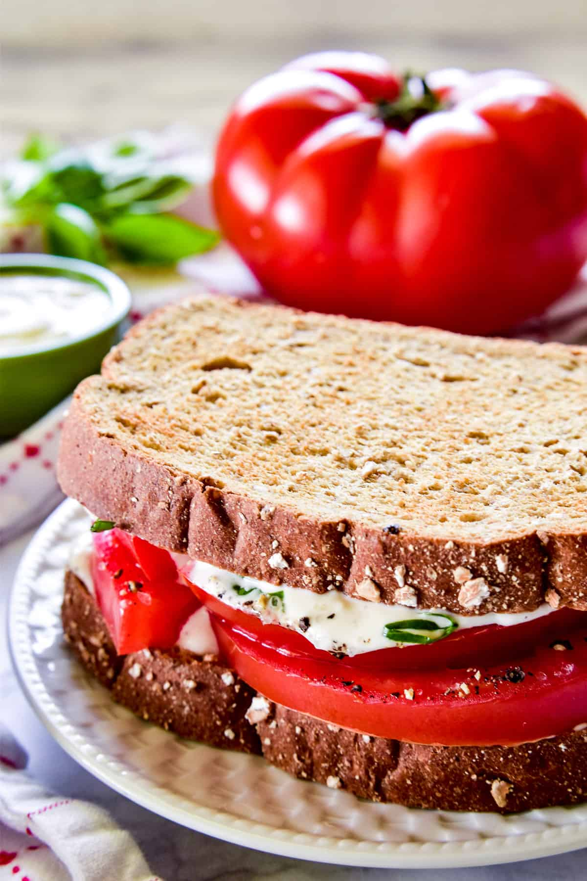 Tomato Sandwich on a white plate with a beefsteak tomato in the background