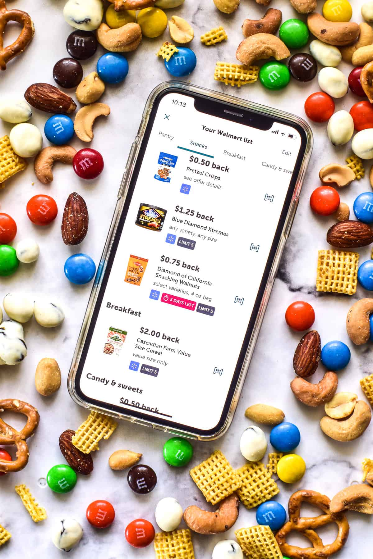 Phone showing Ibotta app surrounded by trail mix