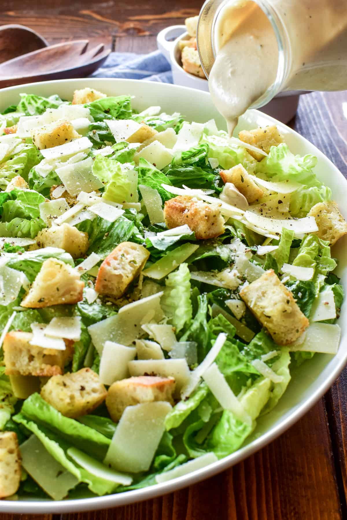 Caesar Dressing being poured onto a salad