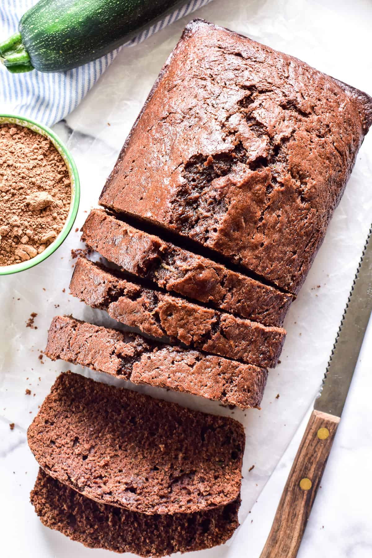 Overhead image of sliced Chocolate Zucchini Bread with a knife