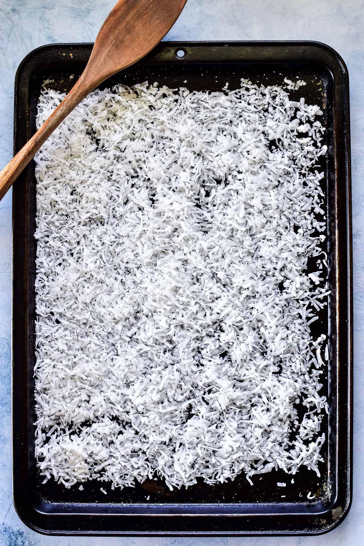 Shredded coconut on a rimmed baking sheet