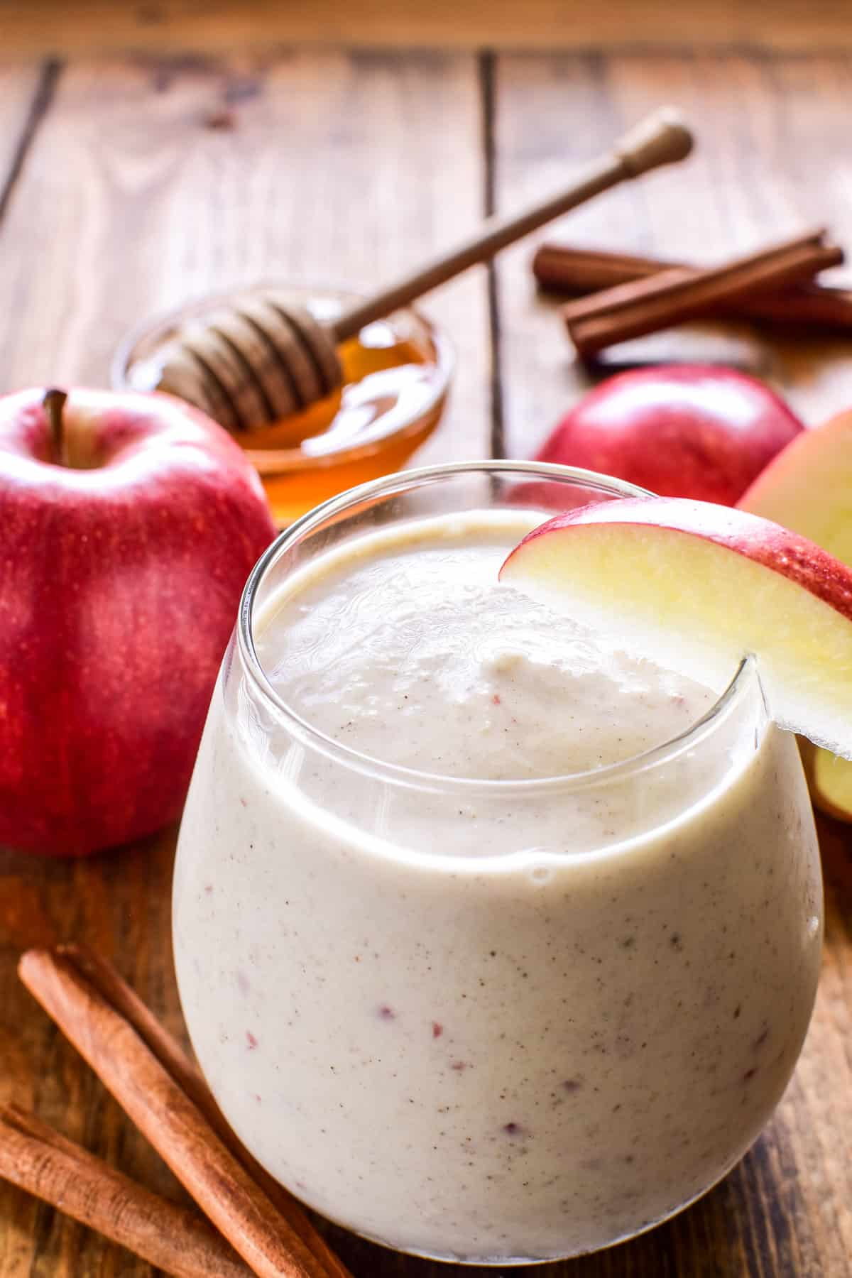 Apple Smoothie in a glass with an apple slice garnish and fresh apples in the background