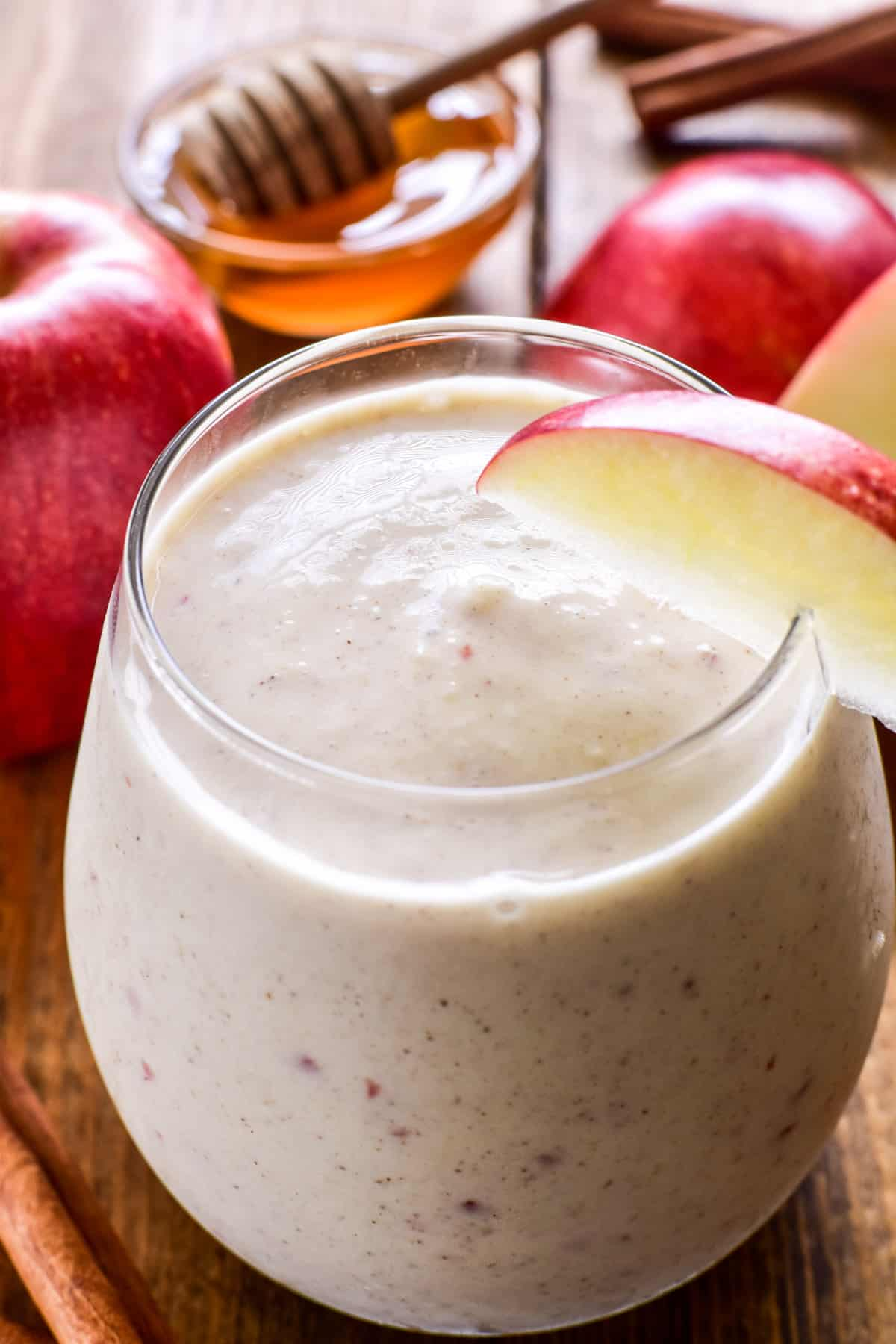 Close up of Apple Smoothie in a glass with fresh apples, cinnamon sticks, and honey