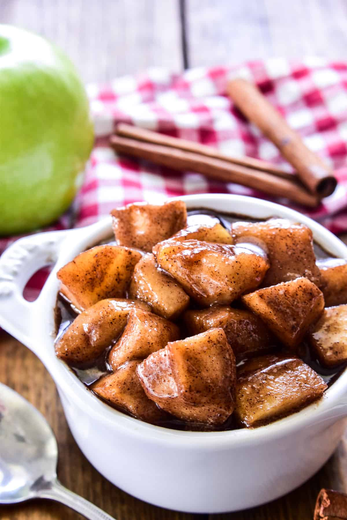 Fried Apples in a small white dish with a red checkered towel and cinnamon sticks